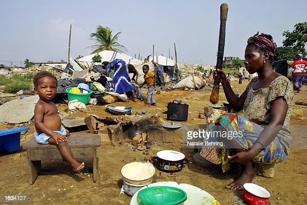 An Ivorian mother prepares dinner in a demolished shanty town March 7 2003 in the capital city Abidjan Ivory Coast There were 131 shanty towns called...