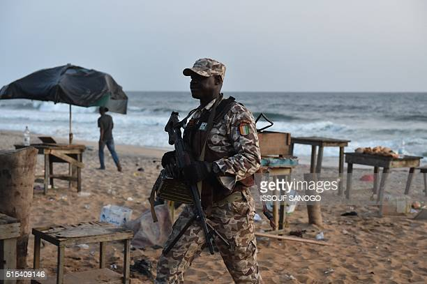 An Ivorian soldier walks on the beach after heavily armed gunmen opened fire on March 13 2016 at a hotel in the Ivory Coast beach resort of...