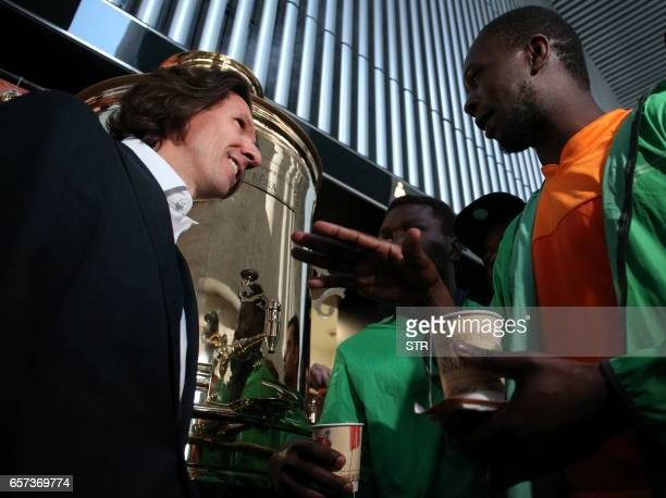 An Ivorian supporter holding a cup of tea from a samovar speaks with Russian football antiracism watchdog Alexei Smertin during an antiracism event...