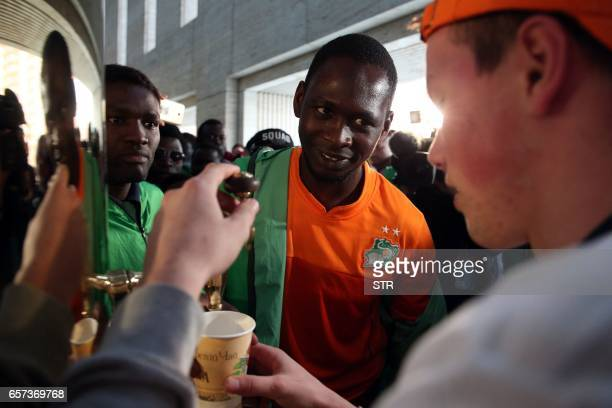 An Ivorian supporter is welcomed with a cup of tea from a samovar during an antiracism event before the start of the international friendly football...