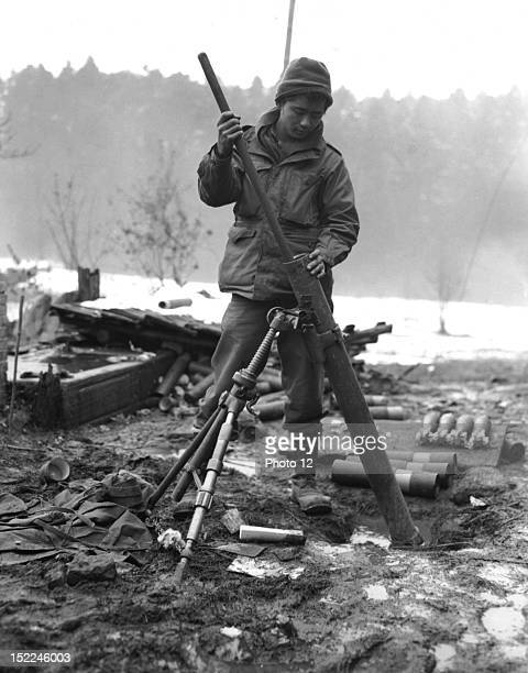 An JapaneseAmerican soldier member of the 442nd Regiment cleans out the barrel of a 81mm mortar in the St Die area November 17 1944