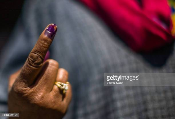 An Kashmiri Muslim woman shows her indelible ink marked finger after casting her vote during the elections of the lower house of the Indian...