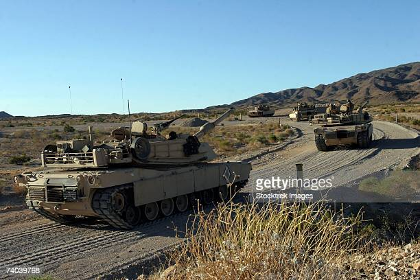 An M1A1 Abrams main battle tanks advance to Table 5, a heavy machine gun assault course at Combat Center Range 500, where they will qualify their crewman in the company's semiannual gunnery exercise.