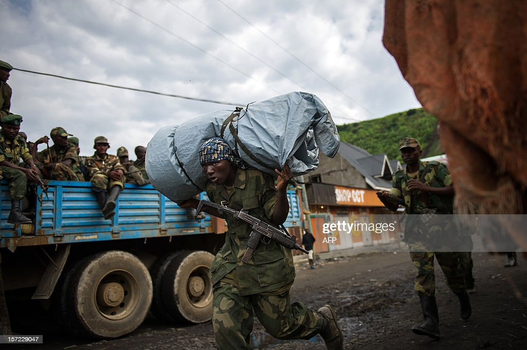 An M23 reebl carries equipment through Sake having left his base in the hills north of the town in the east of the Democratic Republic of the Congo on November 30, 2012. Hundreds of Congolese rebels withdrew on November 30 from frontline positions around Goma as promised under a regionally brokered deal, while police entered the key eastern city to take over control.