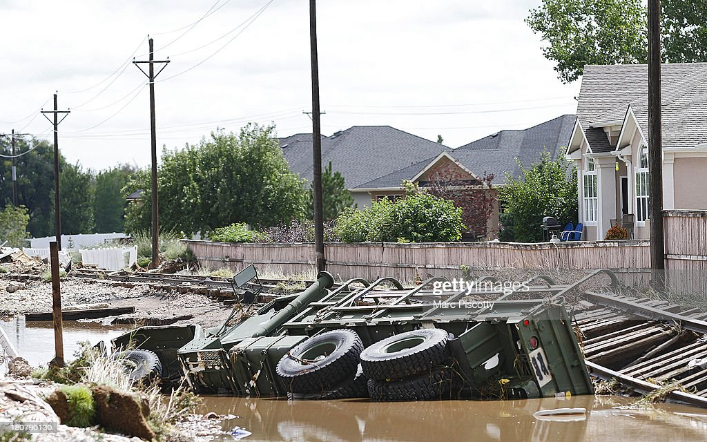 An M-923 United States military logistical transportation vehicle lays on its side in a ditch in Longmont, Colorado after being washed away by flood waters as local residents were cleaning up in the wake of heavy flooding on September 16, 2013 in Longmont, Colorado. More than 600 people are unaccounted for and thousands were forced to evacuate after historic flooding devastated communities in Colorado.