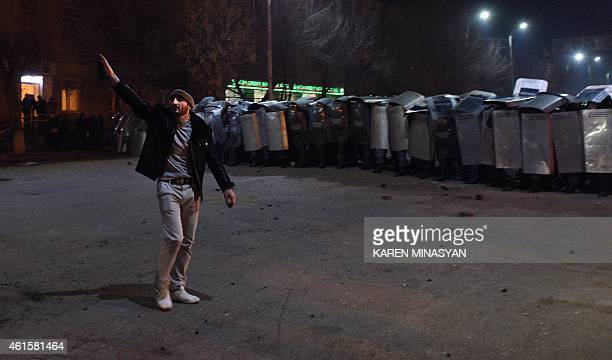 An man gestures next to a row of Armenian police officers holding up their shields as they stand guard during clashes with protesters at a...