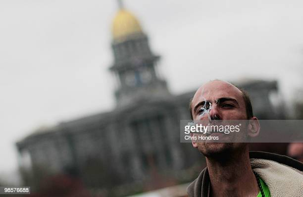 An man smokes marijuana during a promarijuana rally at Civic Center Park with the Colorado State Capitol Building in the background April 20 2010 in...