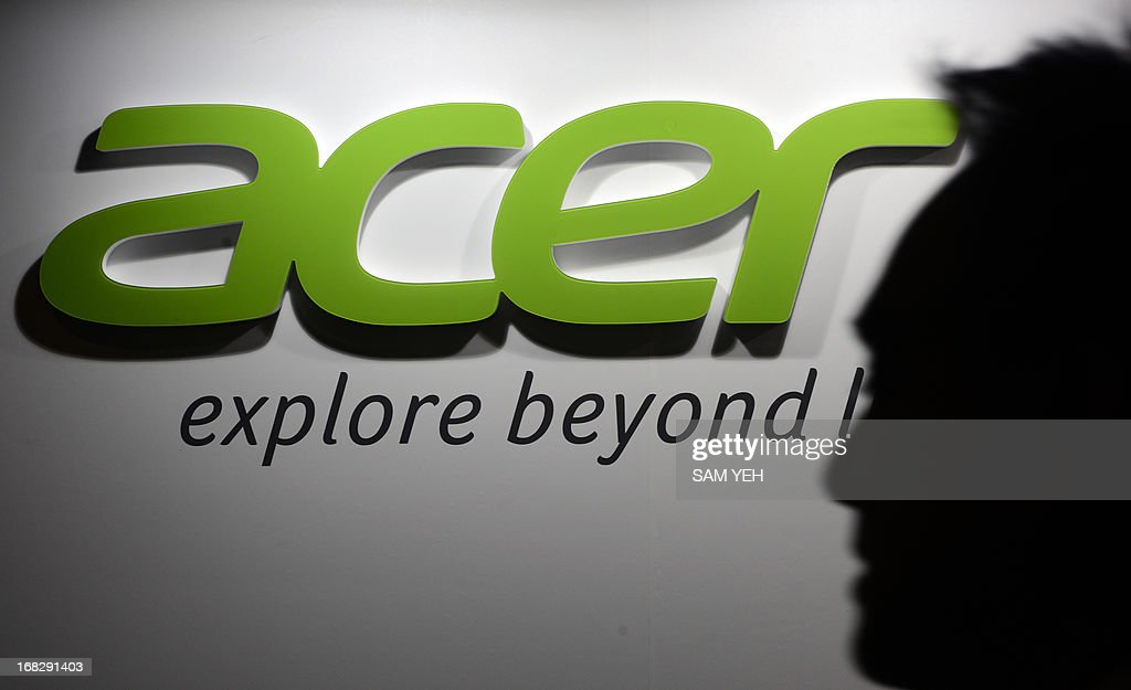 An man walks past an Acer logo during the annual investors' conference in Taipei on May 8, 2013. Taiwan's leading personal computer maker Acer said it swung to profit in the first quarter of 2013 thanks to income from foreign exchange and stock sales. AFP PHOTO / Sam YEH