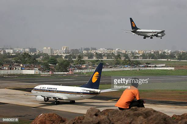 An man watches a Jet Airways Ltd flight landing on the runway in Mumbai India on Wednesday June 27 2007 Jet Airways Ltd the nation's biggest domestic...