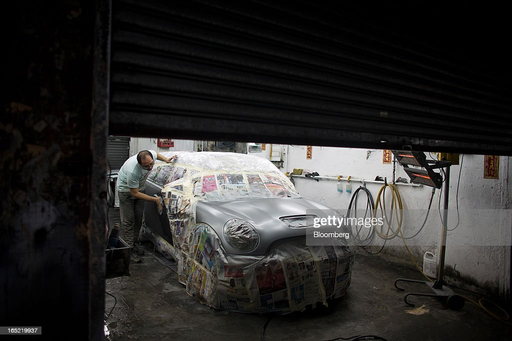 An man wipes down a freshly spray-painted vehicle inside a car-repair shop in the Tai Hang area of Hong Kong, China, on Saturday, March 30, 2013. Rents are climbing in neighborhoods near Causeway Bay and Hong Kong's other prime shopping districts, known for luxury stores that attract free-spending tourists from mainland China. That's squeezing out mom-and-pop shops, congee and noodle vendors as developers and landlords seek to profit from the trend. Photographer: Lam Yik Fei/Bloomberg via Getty Images