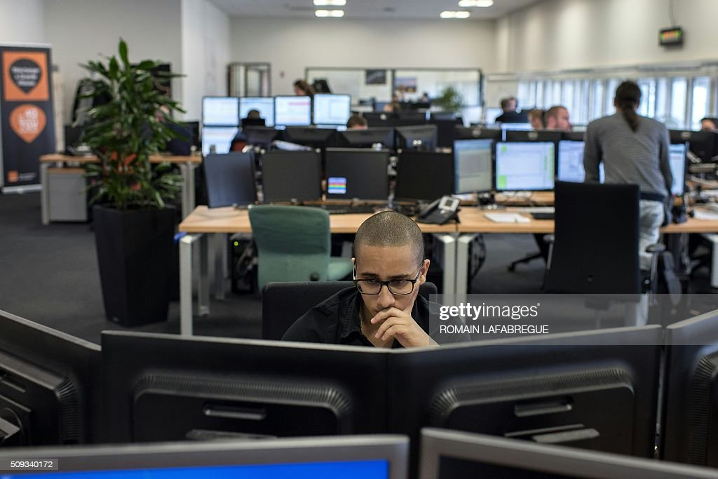 An man works at Orange's mobile phone supervision center in Lyon on February 10, 2016. / AFP / ROMAIN LAFABREGUE