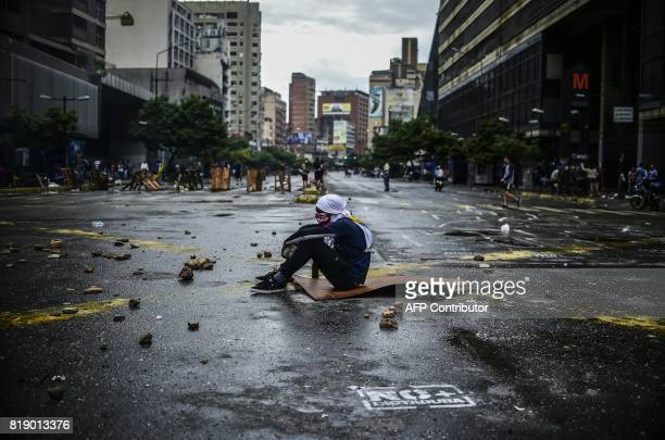 TOPSHOT An masked opposition activist sits on the floor during a blockade to protest against Venezuelan President Nicolas Maduro in Caracas on July...