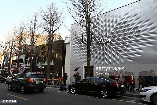 An MCM Holdings AG store right stands next to a Godiva Chocolatier Inc store on Garosugil street in the Gangnam district of Seoul South Korea on...