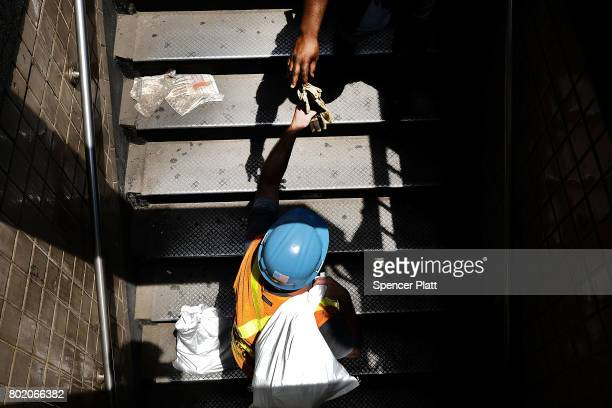 An Metropolitan Transportation Authority worker grabs a glove while entering a Harlem subway station where a morning train derailment occurred on...