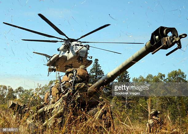 An MH-53E Sea Stallion helicopter preparing to lift an M777 105-mm lightweight Howitzer.