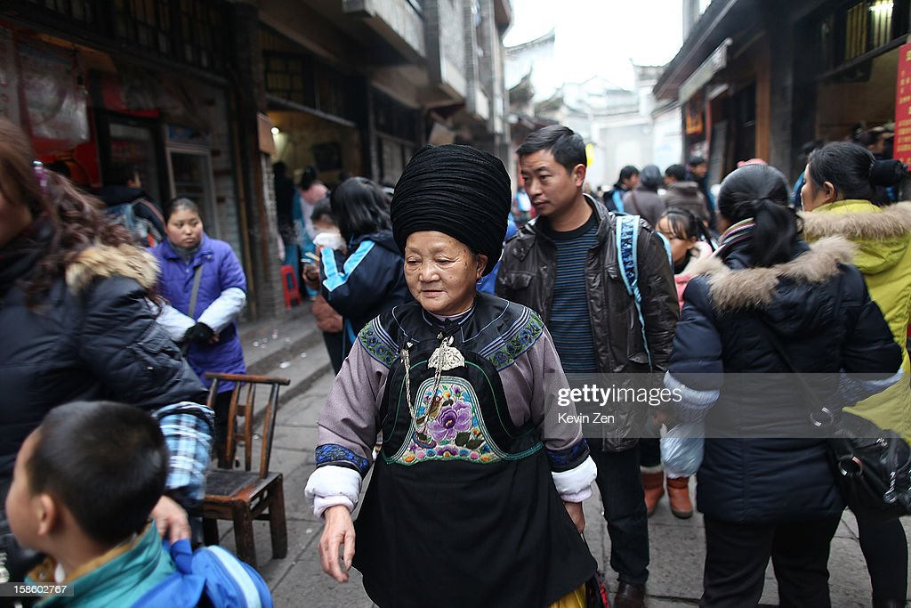 An Miao woman walks in old town, dressed in tradition Miao clothes on December 18, 2012 in Fenghuang, China. Fenghuang Town was built by Emperor Kangxi in 1704 and after 300 years, the city's ancient appearance has been well preserved. Hunan is located in southwest Hunan Provience of China with a population of 370,000 within a total area of 1700 square kilometers.