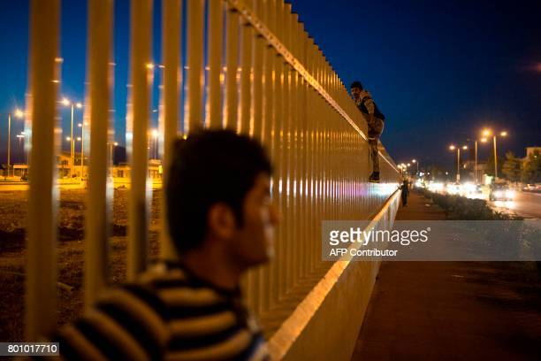 An migrant jumps over a fence into a ferry terminal in Patras southwestern Greece on June 20 2017 Khalid a 13yearold from Afghanistan spends his days...