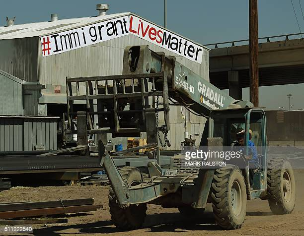 An migrant worker drives a forklift beneath an 'Immigrant Lives Matter' sign outside a steel company in the border town of El Paso Texas on February...