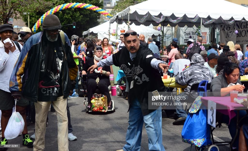 An LA Mission volunteer directs the the homeless on Skid Row to their tables at the annual Good Friday meal hosted by the LA Mission and served by volunteers and celebrities on April 18, 2014 in Los Angeles, California. For more than 75 years, the LA Mission has helped serve the needs of the down and out in downtown Los Angeles, providing emergency service like shelter, food , clothing as well as professional medical and dental services. AFP PHOTO/Frederic J. BROWN