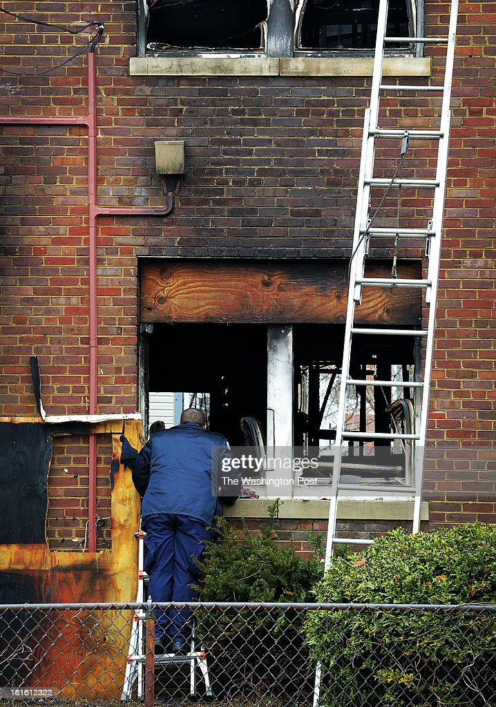 An MPD officer peers through a window in the aftermath of a fire that destroyed a rowhouse at 1704 S Street, southeast, where bodies were discovered, on February, 05, 2013 in Washington, DC.