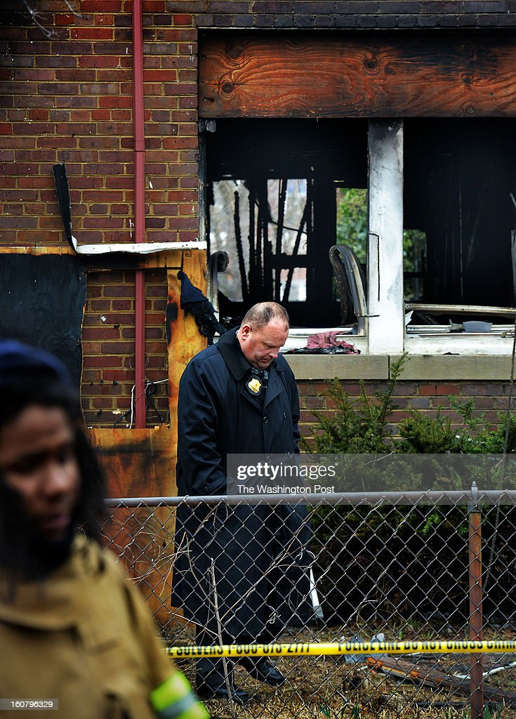 An MPD officer walks in the front yard in the aftermath of a fire that destroyed a rowhouse at 1704 S Street, southeast, where bodies were discovered, on February, 05, 2013 in Washington, DC.