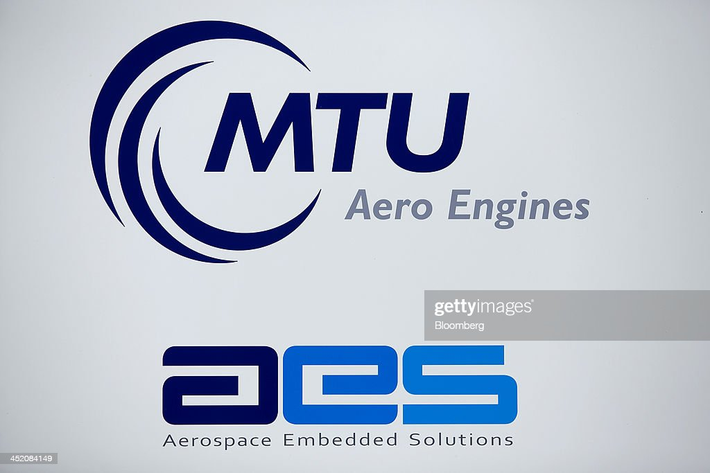 An MTU logo sits above the Aerospace Embedded Solutions GmbH (AES) logo at the MTU Aero Engines headquarters in Munich, Germany, on Monday, Nov. 25, 2013. MTU Aero Engines Holding AG said it will eliminate jobs and cut costs to boost profitability as the German manufacturer predicted strong growth in sales of new engines next year. Photographer: Krisztian Bocsi/Bloomberg via Getty Images