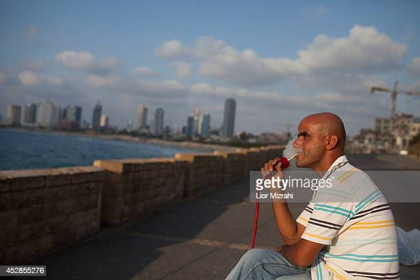 An Muslim Israeli man smokes a hookah on the beach on the first day of Eid alFitr on July 28 2014 in Jaffa Israel As Israel's operation 'Protective...