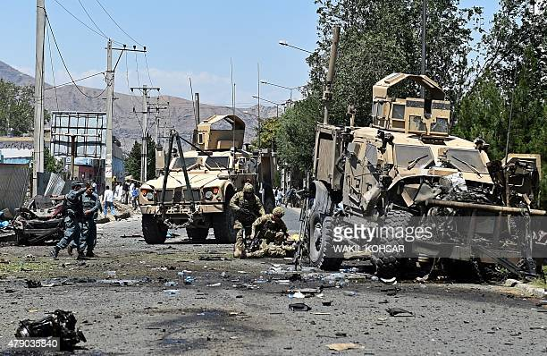 An NATO soldier helps a colleague who was injured in a suicide car bomb attack that targeted foreign military vehicles in the Afghan capital Kabul on...