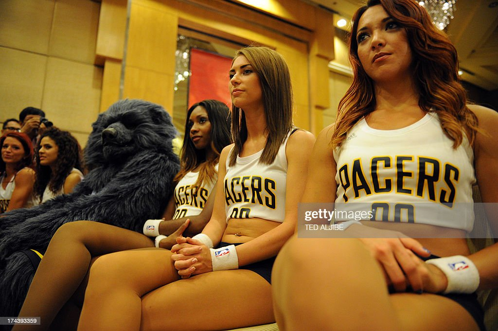 An NBA basketball team Memphis Grizzlies mascot (C) sits beside members of the Pacemates cheerleaders as they listen to NBA players James Harden of the Houston Rockets and Eric Gordon of the New Orleans Pelicans (not pictured) at a press conference in Manila on July 25, 2013. Harden and Gordon are in Manila to promote the NBA pre-season games dubbed 'NBA 3X Asia' slated for October 2013. AFP PHOTO/TED ALJIBE