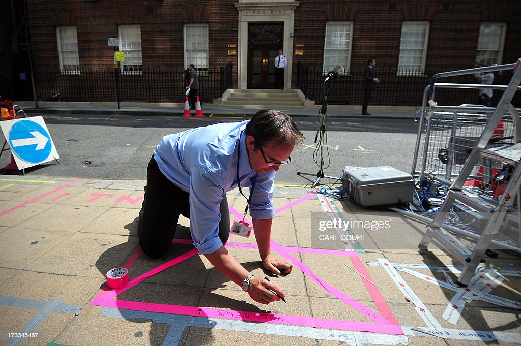 An NBC employee sticks tape to the ground to mark-up a spot outside the Lindo Wing of Saint Mary's Hospital in London, on July 12, 2013, where Prince William and his wife Catherine's baby will be born. Britain's royal family and the world's media are on tenterhooks awaiting the birth of Prince William and wife Catherine's first child, a baby who will one day be king or queen of Britain and a diverse group of commonwealth countries.