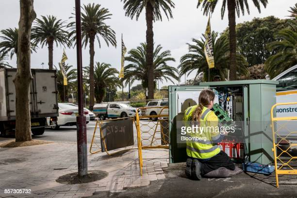 An NBN Co technician handles hardware in a fiber distribution cabinet during the installation of fibertothebuilding connections in Sydney Australia...