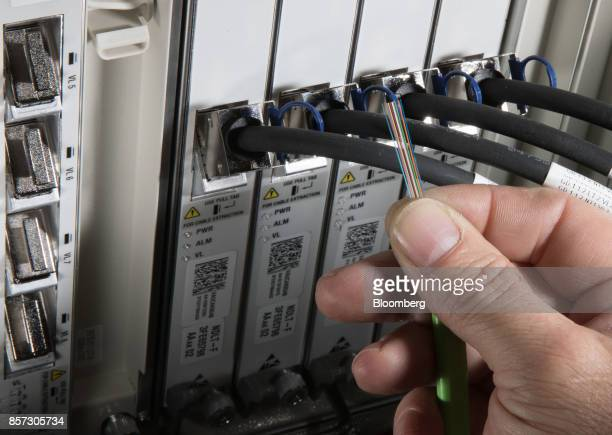 An NBN Co technician holds a cable showing 12 strands of optical fiber in front of a distribution cabinet during the installation of...