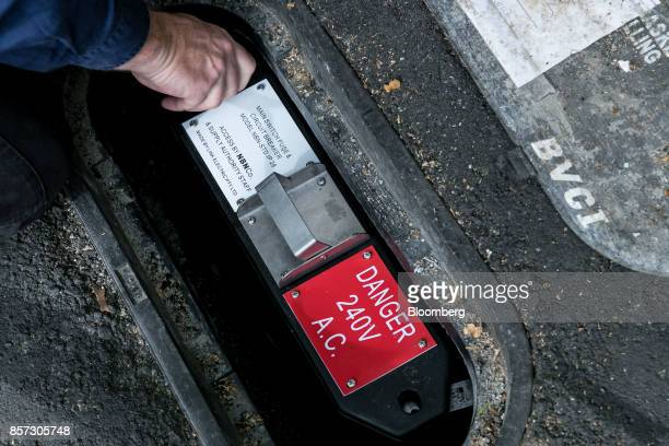 An NBN Co technician opens the power supply and circuit breaker through an access port in a sidewalk during the installation of fibertothebuilding...