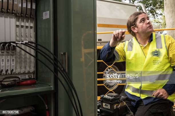 An NBN Co technician sits next to a fiber distribution cabinet during the installation of fibertothebuilding connections in Sydney Australia on...