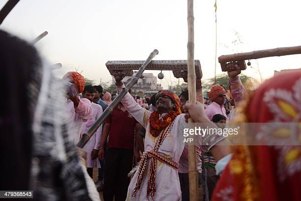 An ndian reveller carries a wooden stick to 'defend' himself during a ritual which sees the village's women 'beat' the men during during Lathmar Holi...