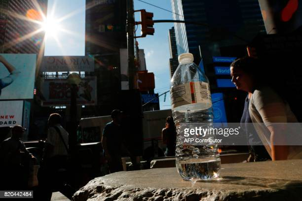 An near empty bottle of water is seen in Times Square during a sunny day as hot temperatures continue in New York on July 21 2017 / AFP PHOTO /...