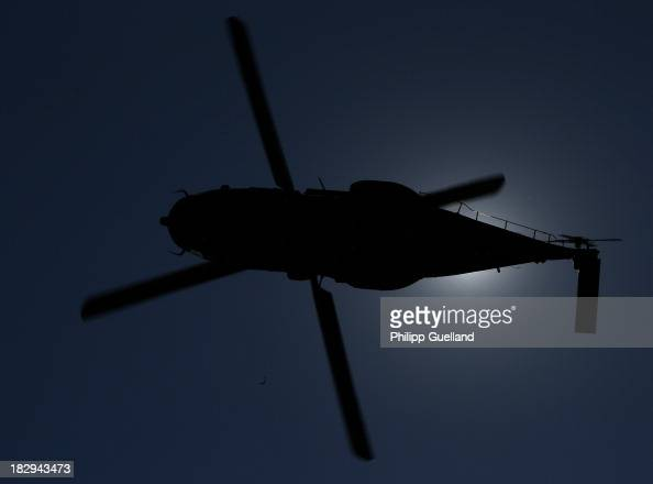 An NH90 helicopter is silhouetted while flying during the annual military exercises held for the media at the Bergen military training grounds on...
