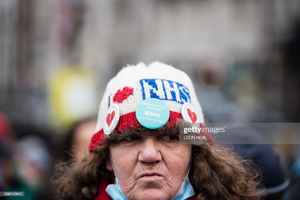 An NHS supporter wears a pro-NHS hat as she takes part in a demonstration in central London on February 6, 2016. The march saw thousands listen to speeches from medical professionals, as well as designer Vivienne Westwood and actress Vanessa Redgrave, before heading to Downing Street where they staged a silent protest. / AFP / LEON NEAL
