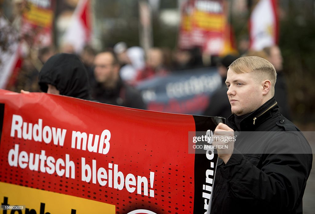 An NPD supporter holds a banner reading 'Rudow must stay German' during a protest in the south east Berlin area of Rudow on November 24, 2012. Protestors from the German far-right party NPD (National Democratic Party of Germany) gathered to oppose new asylum seeker housing in the area and faced counter demonstrations enroute .