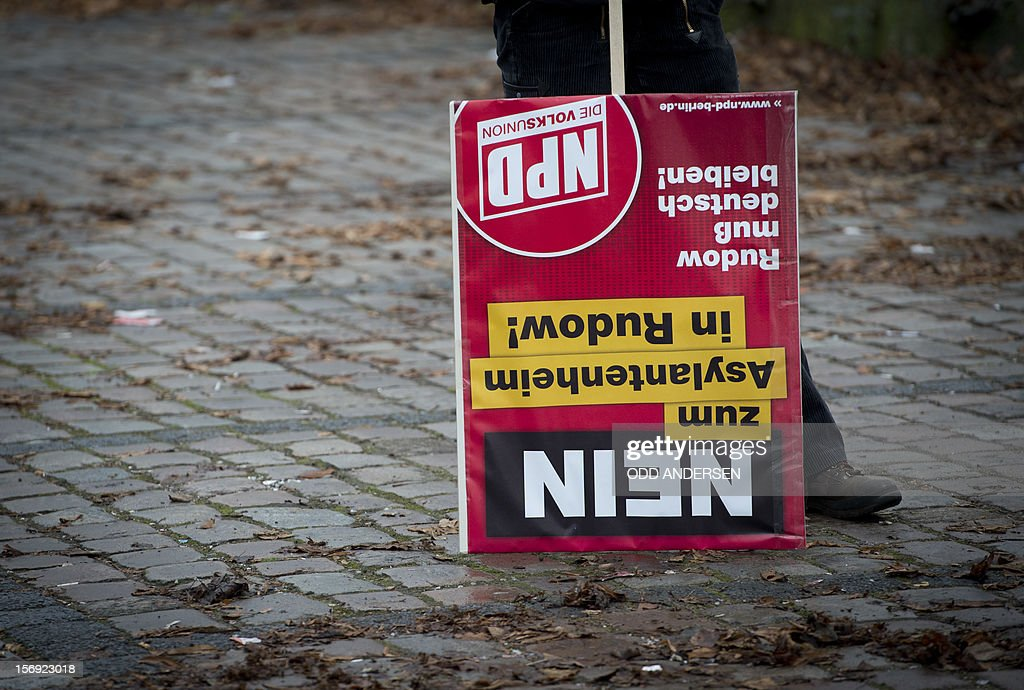 An NPD supporter holds a placard upside down reading (No to asylum seekers housing in Rudow) during a protest in the south east Berlin area of Rudow on November 24, 2012. Protestors from the German far-right party NPD (National Democratic Party of Germany) gathered to oppose new asylum seeker housing in the area and faced counter demonstrations enroute .