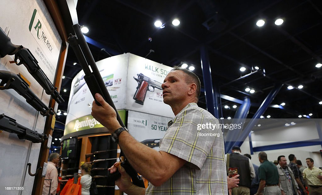An NRA attendee looks through the scope of a Freedom Group Inc. Remington brand gun during the 2013 National Rifle Association Annual Meetings & Exhibits at the George R. Brown Convention Center in Houston, Texas, U.S., on Saturday, May 4, 2013. After the U.S. Senate defeated a proposed expansion of background checks on gun purchases, the NRA's annual conference has a celebratory atmosphere. Yet as the festivities began, gun-control advocates swarmed town halls, organizing petitions and buying local ads to pressure senators from Alaska to New Hampshire to reconsider the measure that failed by six votes on April 17. Photographer: Aaron M. Sprecher/Bloomberg via Getty Images