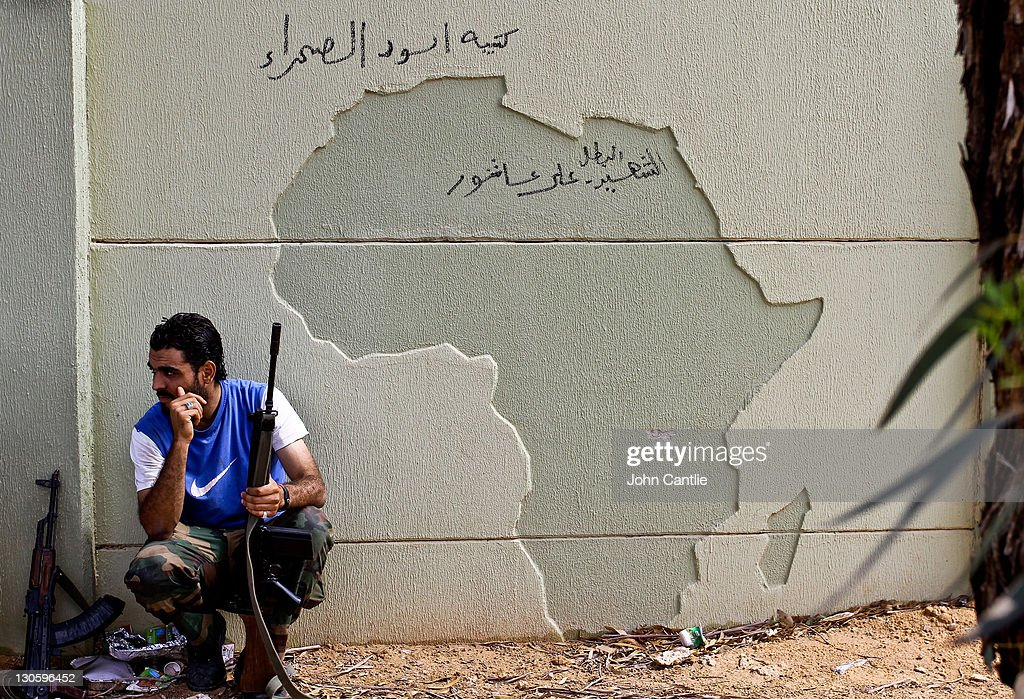 An NTC fighter takes cover behind a concrete wall emblazoned with the continent of Africa in Colonel Gaddafi's home city of Sirte on October 14, 2011 in Libya. NTC forces are continuing their advance on Colonel Muammar Gaddafi's hometown of Sirte.