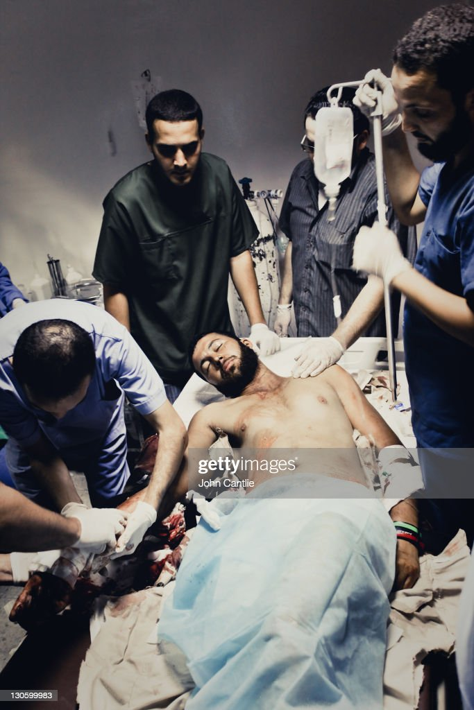 An NTC fighter wounded during the first assaults into Colonel Gaddafi's home city of Sirte, is treated in a field hospital on September 18, 2011in Libya. NTC forces are continuing to advance on Colonel Muammar Gaddafi's home town of Sirte.
