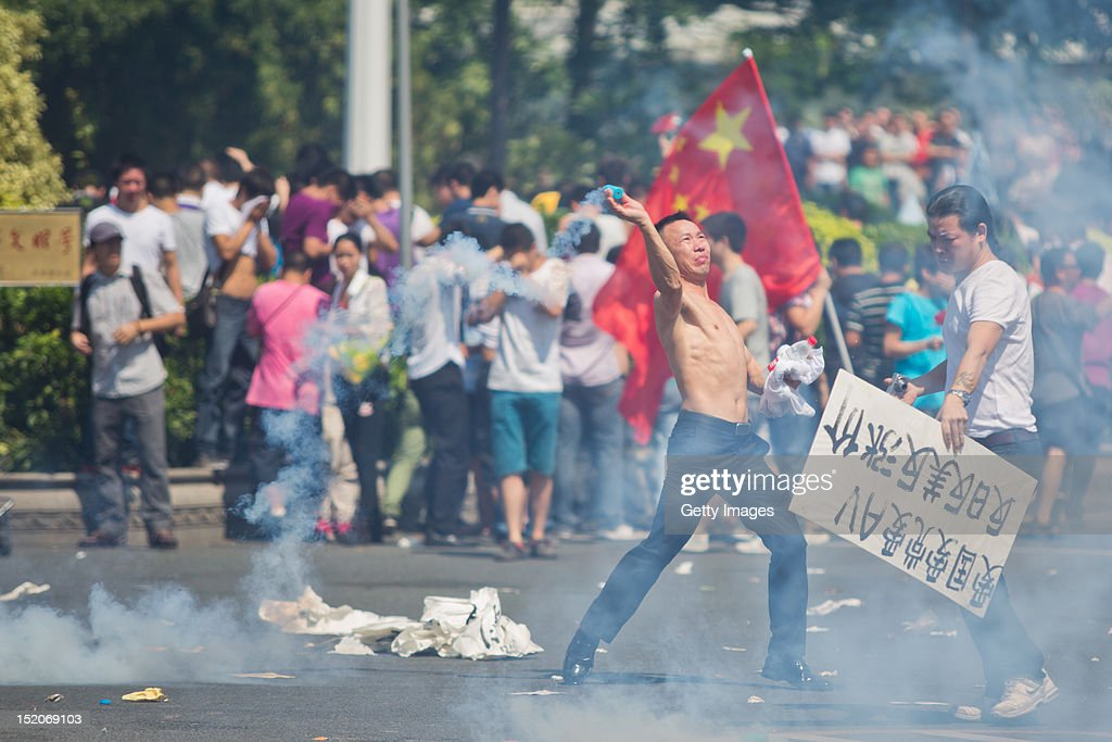An ntiJapanese protester throws a gas cannister as they demonstrate over the disputed Diaoyu Islands on September 16 2012 in Shenzhen China Protests...