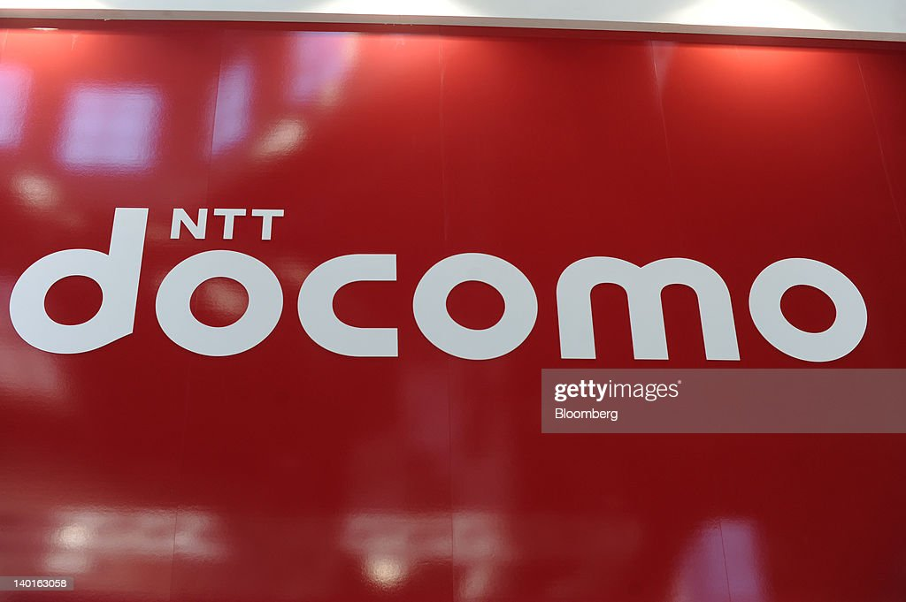 An NTT DoCoMo Inc. logo sits on display at the company's booth at the Mobile World Congress in Barcelona, Spain, on Wednesday, Feb. 29, 2012. The Mobile World Congress, operated by the GSMA, expects 60,000 visitors and 1400 companies to attend the four-day technology industry event which runs Feb. 27 through March 1. Photographer: Denis Doyle/Bloomberg via Getty Images