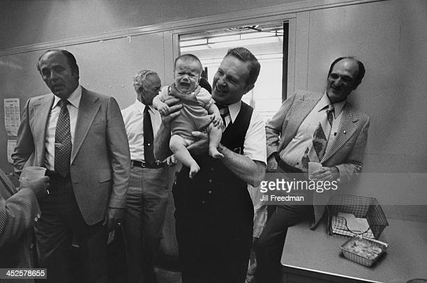 An NYPD detective holds a crying baby during a retirement party in the detectives squad room New York City 1980