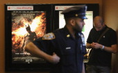 An NYPD officer keeps watch inside an AMC move theater where the film 'The Dark Knight Rises' is playing in Times Square on July 20 2012 in New York...