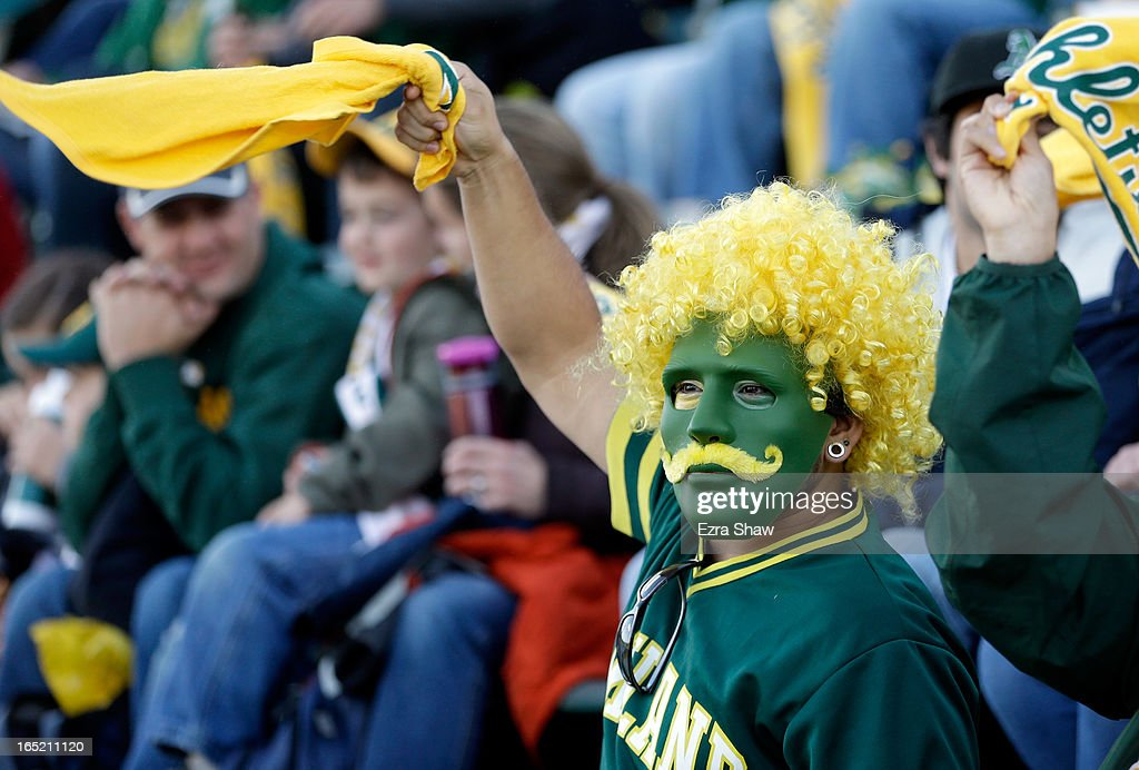 An Oakland Athletics fan cheers for the Athletics during a pregame ceremony before their game against the Seattle Mariners on Opening Day at O.co Coliseum on April 1, 2013 in Oakland, California.