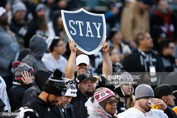 An Oakland Raiders fan holds a 'Stay In Oakland' sign during the game against the San Diego Chargers at Oco Coliseum on December 24 2015 in Oakland...