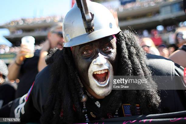 An Oakland Raiders fan in the Black Hole cheers on his team during their game against the New England Patriots at Oco Coliseum on October 2 2011 in...
